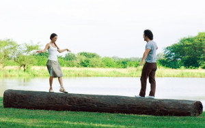 Couple standing on log, approaching each other